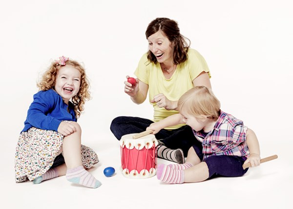 A mom plays instruments and sings with her children in a Music Together class.